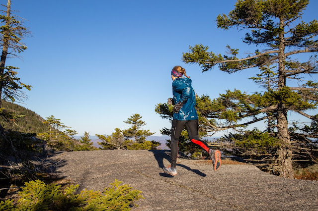 Women in blue gore jacket runs away from camera along exposed rock ledge