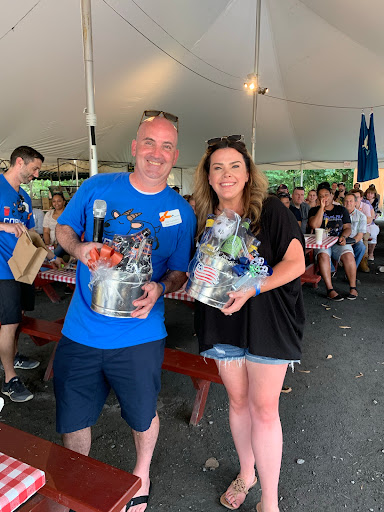 Two employees posing with the gift baskets they won