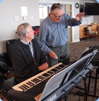 Michael Bramley playing a Yamaha PSR-S950 with Roy Steen discussing some technical points. Photo courtesy of Diane Lyons.
