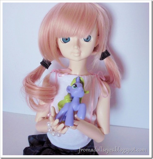 A ball jointed doll holding her new My Little Pony figure.