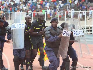Les éléments de la police nationale Congolaise entourent les arbitres en courant, ce 20 mars 2011 au stade des matyrs à Kinshasa, lors du match V Club de Kinshasa et Coton sport de Garuwa du Cameroun. Radio Okapi / Photo John Bompengo