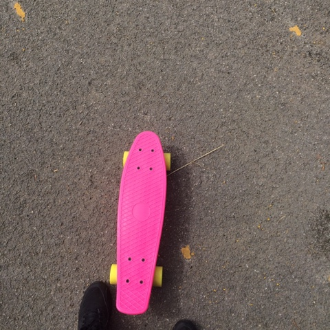 Pink Skateboard with yellow wheels in the park