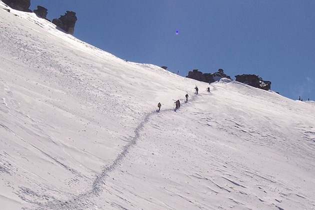 people hiking to the summit of treble cone, wanaka