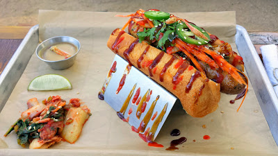 Dak Bulgogi, Bulgogi Chicken Sausage topped with sriracha, kimchi, oyster sauce, cilantro, carrots, and jalapenos on a kolache bun with a side of soy caramel lime. Served with a house made kimchi salad and sun dried shrimp chips. From Banger's Sausage House and Beer Garden in Austin, Texas