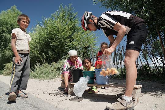 Frau mit Kindern verkaufen Aprikosen an der Straße