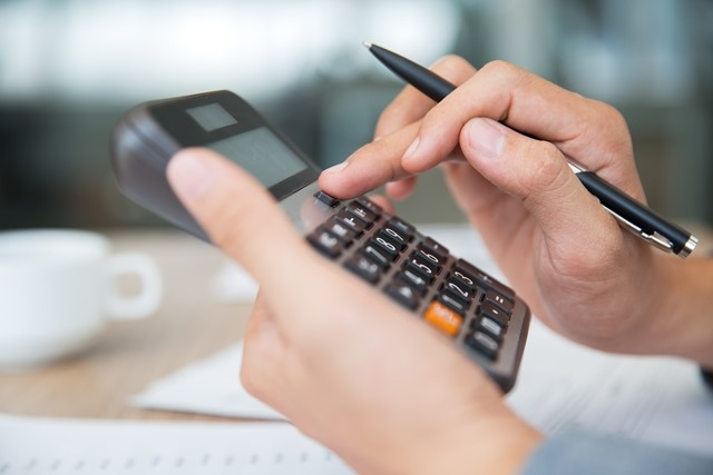 Close-up of male hands using calculator. Unrecognizable accountant holding pen when pushing button on calculator. Finance concept
