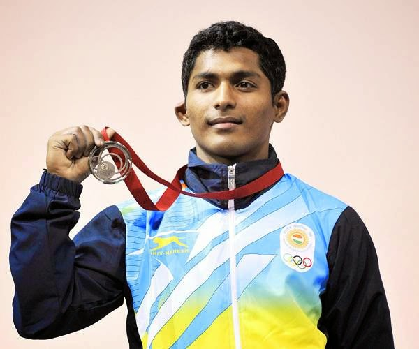 India's gold medalist Sukhen Dey celebrates with his medal on the podium at the medal ceremony for the men's weightlifting 56kg class at the SECC Precinct during the 2014 Commonwealth Games in Glasgow, Scotland on July 24, 2014.