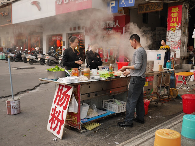 two women wait as a man cooks at a rice noodle roll (肠粉) street food stall in Jieyang, China