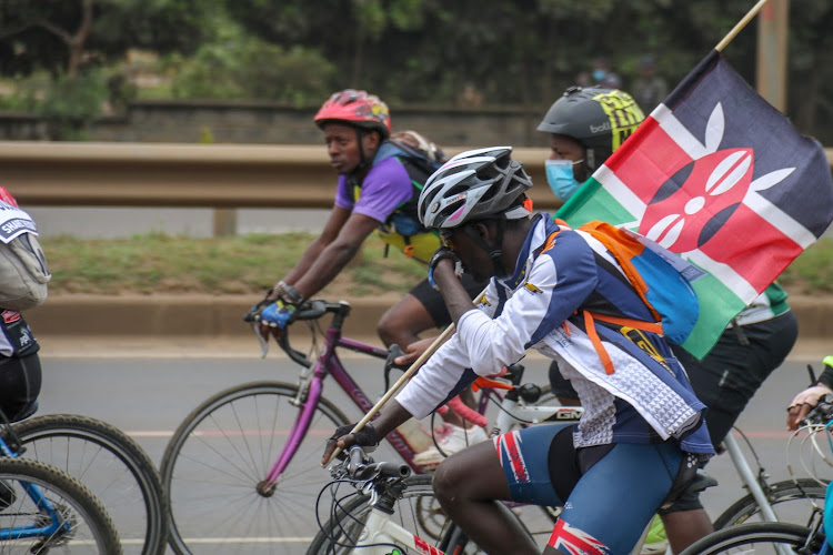 Cyclist Nichole Rider holding a Kenya flag during a peaceful ride in memory of Caleb Omwoyo on September 19 2020.