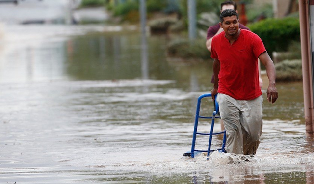 A pedestrian in Phoenix walks through a flooded street with a hand truck to get sand bags to deliver to local businesses during a flash flood as a result of heavy rains on Tuesday, 2 October 2018. Photo: Ross D. Franklin / AP Photo