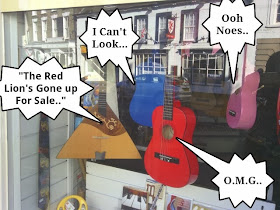 Guitars hanging in a shop window with speech bubbles talking about pub for sale in window reflection