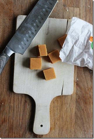 En skärbräde med kniv och fudgebitar, redo att skäras i mindre bitar.