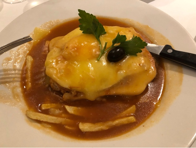 Francesinha : Portuguese toasted sandwich in a pool of spicy sauce