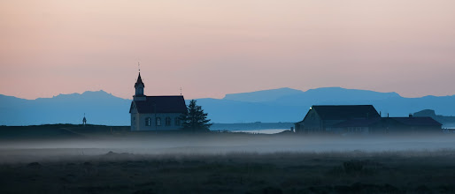 Photo: The Church in the Fog - Iceland  I was driving along the southern coast of Iceland on the way to Vik, and I started going throw an area of lowlands.  Around midnight or so, the sun was getting pretty low in the west, and it gave the sky a slight pink glow in almost every direction.  I shot this one at a 200mm at F/6.7.  I don't often take out my zooms for landscapes, but it does provide a nice compression that gives an unexpected feel to the final photo.  It's really hard to explain in words, but maybe you can sense of this framing in the final result.  It just can't be done with a wide-angle lens, even if I was a lot closer.  from the blog www.stuckincustoms.com