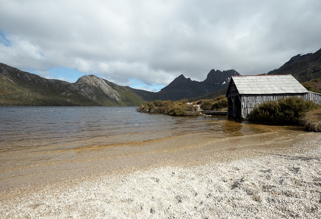 The old boat shed on Dove Lake with remnants of snow on Cradle Mountain in the distance