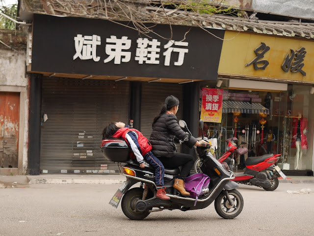 child sleeping on a moving scooter in Jieyang, China