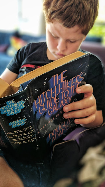 Boy reads the hardback edition of The Hitch Hikers Guide To The Galaxy omnibus