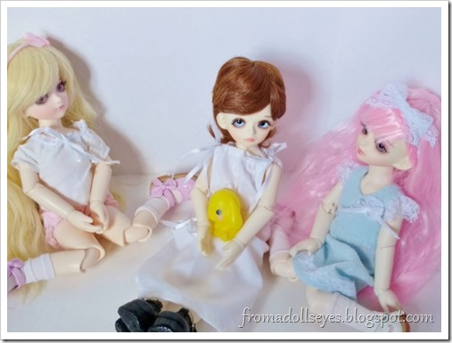 Three little yosd sized ball jointed dolls sitting nicely together.  On the left is the blond haired noisy bjd (Sakura), and the right is the pink haired quiet bjd (Yuna).  Sitting between them is a little boy bjd with brown hair (Makoto).  They play well together.
