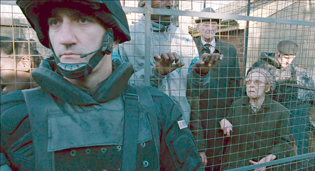 In this screenshot from the film, 'Children of Men', refugees are caged in the street in London 2027. An elderly German woman complains to a guard about 'die Schwarzen' with whom she is caged. Photo: Alfonso Cuarón