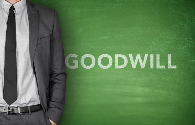 Man standing next to a chalkboard that says GOODWILL