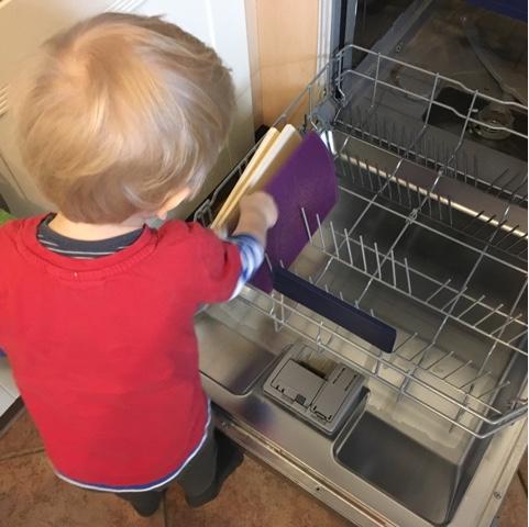 Kind räumt Geschirrspüler aus