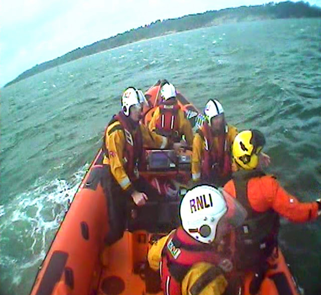 Volunteer helmsman Gavin McGuinness manoeuvres the ILB as the winchman prepares to be winched back up to the helicopter with the casualty - 10 May 2014. Photo credit: RNLI Poole (taken by the onboard camera)