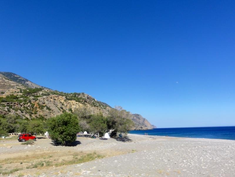 En strand med biler og telt.