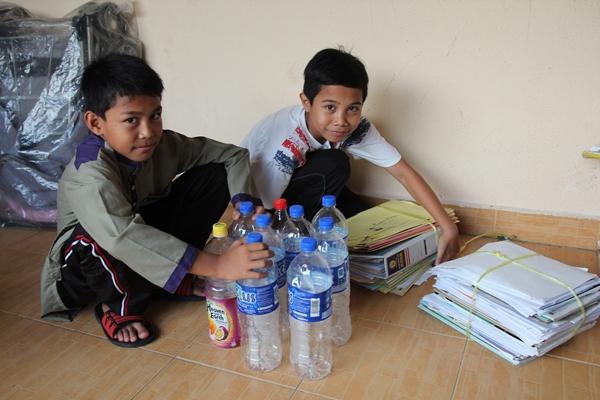 anak-anak membantu asing botol pelastik dan kertas
