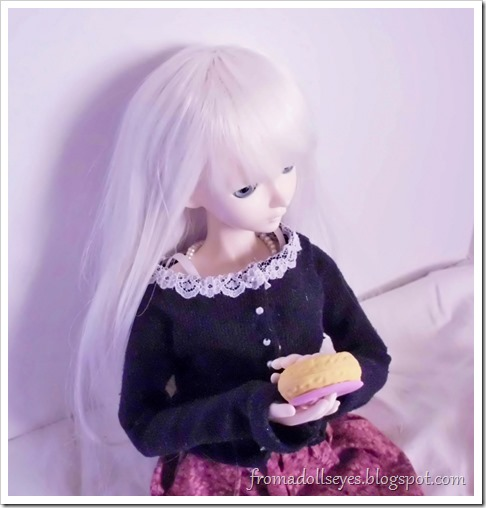 A ball jointed doll with a donut.