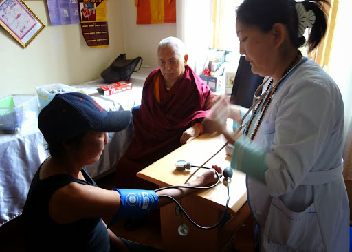 Lama Zopa Rinpoche watches as a woman receives care at Lamp of the Path's health clinic, Ulaanbaatar, Mongolia, September 3, 2013. Photo by Ven. Roger Kunsang.