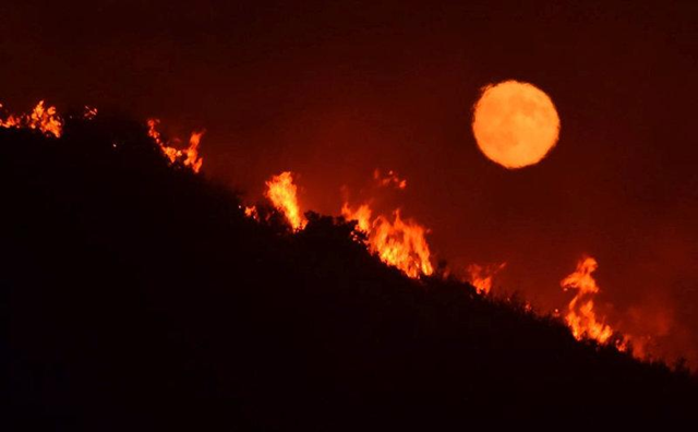 The full moon rises over flames of the Alamo fire on a hilltop off Highway 166 east of Santa Maria, California, U.S., 7 July 2017. Photo: Mike Eliason / Santa Barbara County Fire Dept / REUTERS