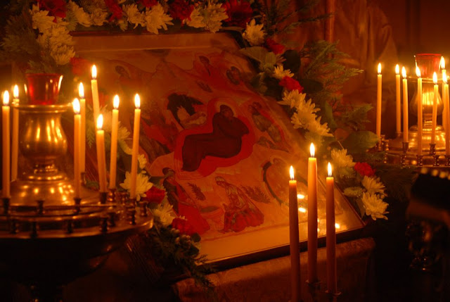 The icon of the Nativity, adorned with flowers, during the Christmas Eve vigil.