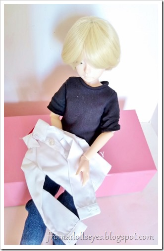A white button down shirt for a msd or 1/4 scale ball jointed doll, bought from Alice's Collections.  It is being held by its new owner, and male ball jointed doll with blond hair (Yuki).