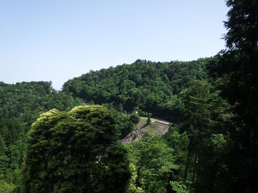 谷の向こうに林道と地蔵峠(左)