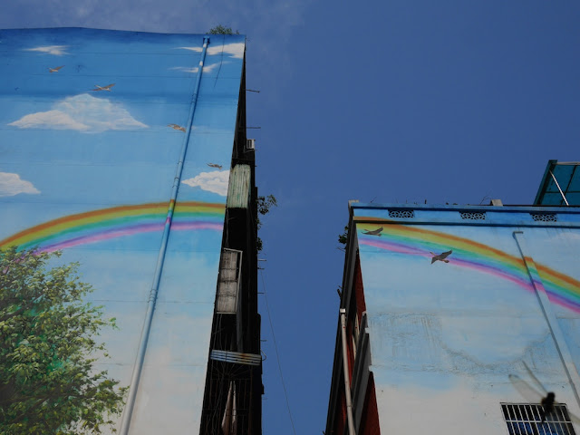 two buildings with a painted rainbow, blue sky, and birds with a real blue sky in the background