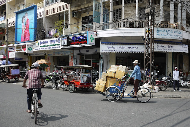 man carrying boxes on a cyclo (pedal rickshaw)