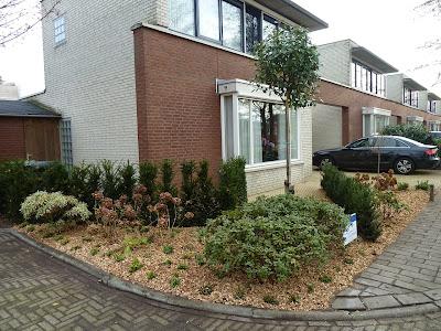 Strakke achtertuin met vijver, kunstgras en pergola