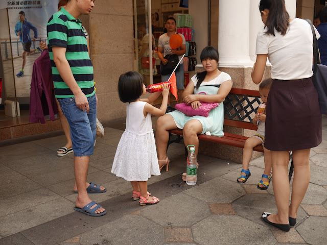 young girl drinking a bottle of sweetened herbal tea and holding a PRC flag in Zhongshan, China