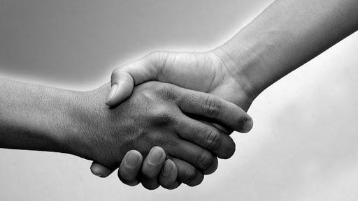 Qual é a origem do aperto de mãos
