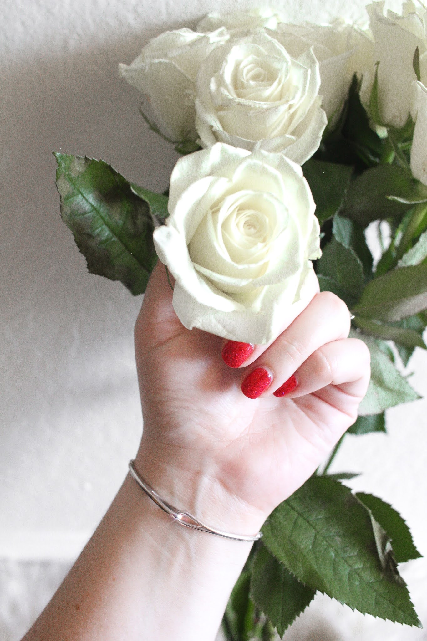 woman's hand with red nail polish holding a white rose and wearing a white gold bracelet