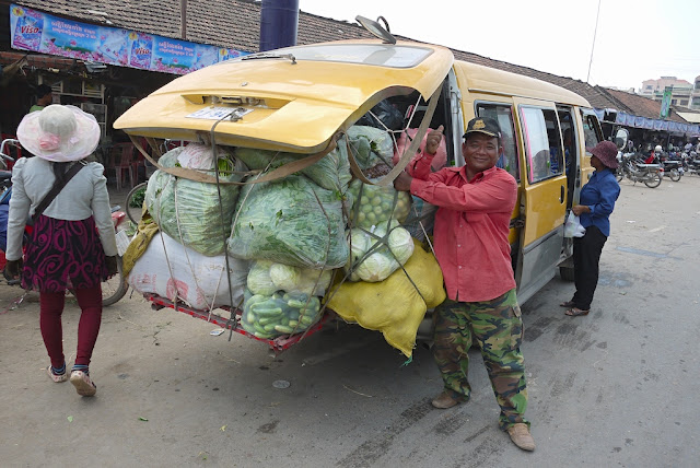 man posing next to a van with its back door open to pack in more vegetables