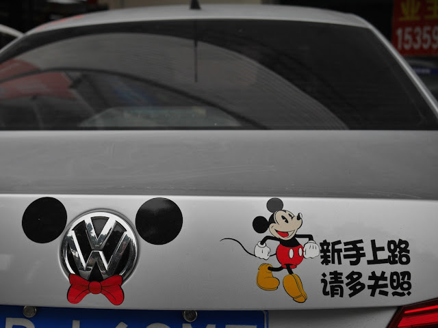 "Mickey Mouse decals on a car with ""新手上路 请多关照"""