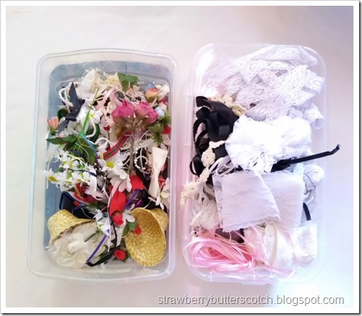 Two plastic bins full of laces, ribbons, bows, flowers and other embellishments.  These will be used to make the plastic caddy all pretty.