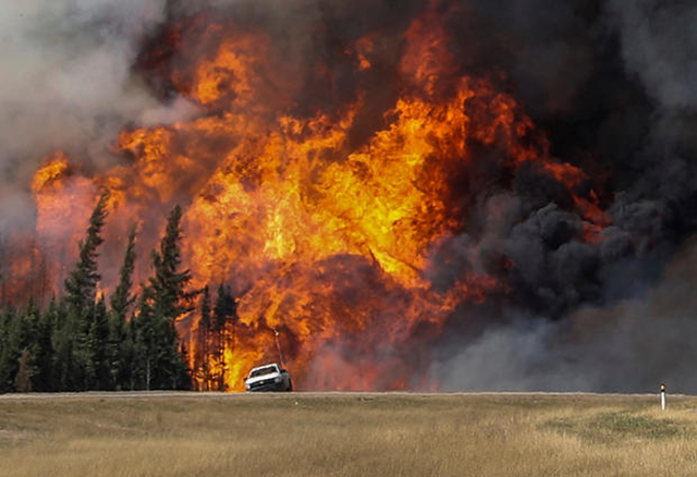 Smoke and flames from the wildfires erupt behind a car on the highway near Fort McMurray, Alberta, Canada, 7 May 2016. Photo: Mark Blinch / REUTERS
