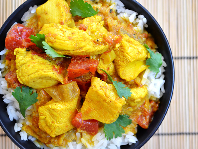 Top view of a bowl of Turmeric Chicken on white rice