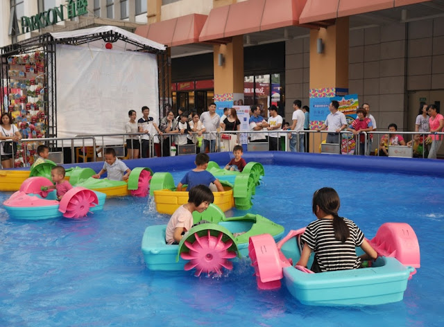 children riding plastic bumper boats