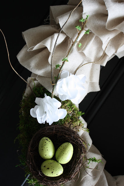 Up close shot of the ruffled wreath, and birds nest with eggs inside of it.