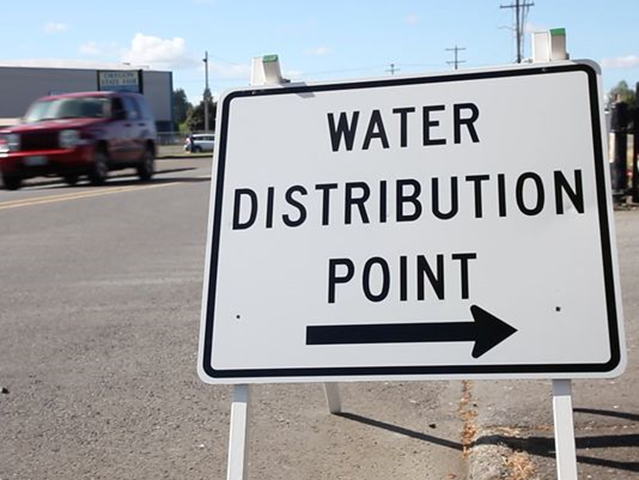 A sign points to one of the water distribution points at the Oregon State Fairgrounds Friday morning, 1 June 2018, in Salem, Oregon. Residents were filling up jugs to the 5-gallon limit, shoring up their drinking water reserves. There are seven locations that will be open around the clock until the water advisory is lifted. Photo: Kelly Jordan / Statesman Journal