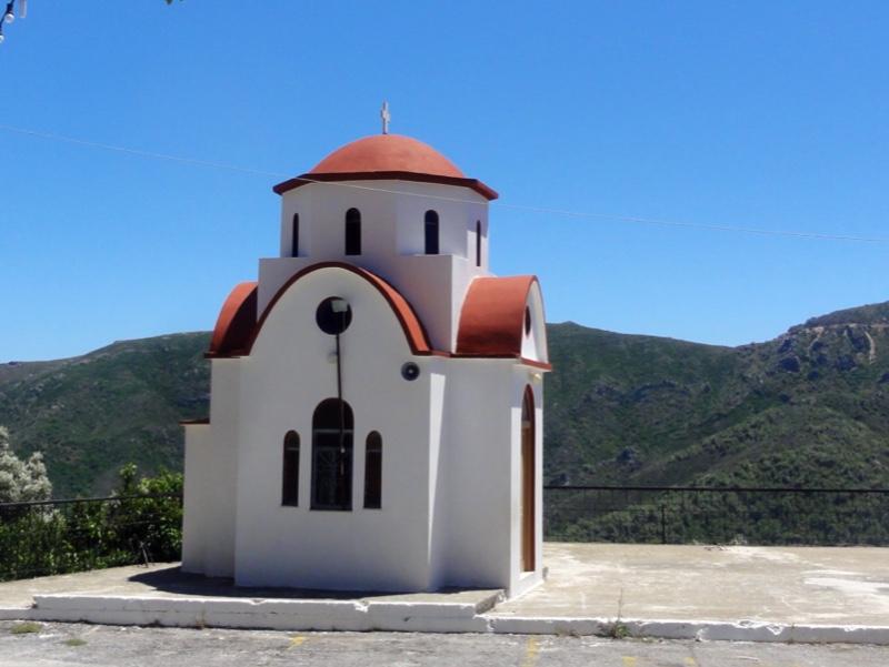 En liten, hvit kirke med rød kuppel. Kun noen få meter langs hver vegg. Grønn ås i bakgrunnen.