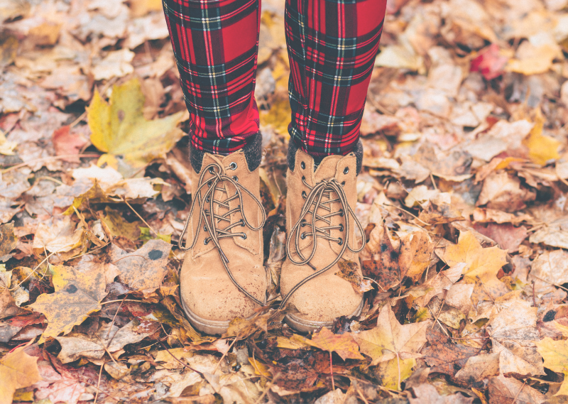 Somebody walking on fallen leaves in a post about five simple ways to feel cosy this Autumn.